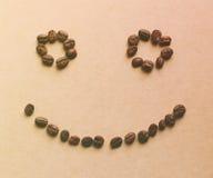 Πρόσωπο που διαμορφώνεται ευτυχές των φασολιών καφέ στοκ εικόνες