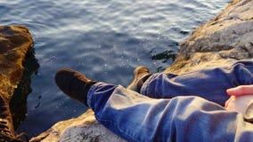 Πρόσωπο που κάθεται στους βράχους από το νερό στον ήλιο βραδιού στοκ φωτογραφία