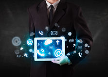 Πρόσωπο που κρατά μια ταμπλέτα με τα μπλε εικονίδια και τα σύμβολα τεχνολογίας Στοκ φωτογραφία με δικαίωμα ελεύθερης χρήσης