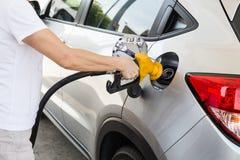 Πρόσωπο που κρατά την κίτρινη βενζίνη πλήρωσης ακροφυσίων στο αυτοκίνητο στοκ φωτογραφίες