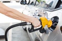 Πρόσωπο που κρατά την κίτρινη βενζίνη πλήρωσης ακροφυσίων στο αυτοκίνητο στοκ εικόνες με δικαίωμα ελεύθερης χρήσης