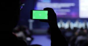 Πρόσωπο που παίρνει το βίντεο και τις φωτογραφίες στο κινητό smartphone στη διάσκεψη Πράσινη οθόνη με τη μεταλλίνη luma συμπεριλα φιλμ μικρού μήκους