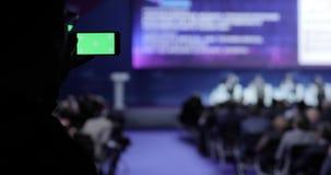 Πρόσωπο που παίρνει το βίντεο και τις φωτογραφίες στο κινητό smartphone στη διάσκεψη Πράσινη οθόνη με τη μεταλλίνη luma συμπεριλα απόθεμα βίντεο