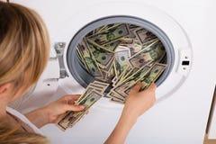 Πρόσωπο που παρεμβάλλει τα χρήματα στο πλυντήριο Στοκ Φωτογραφίες