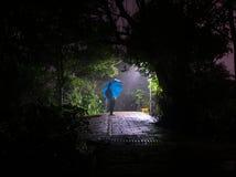 Πρόσωπο που περιμένει με την μπλε ομπρέλα τη νύχτα στη βροχή στοκ φωτογραφίες