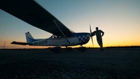 Πρόσωπο που στέκεται κοντά στο αεροπλάνο του σε ένα υπόβαθρο ηλιοβασιλέματος Μικρή έννοια αεροπορίας απόθεμα βίντεο