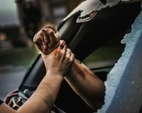 Πρόσωπο που τραβά ένα άλλο πρόσωπο από το σπασμένο παράθυρο ενός αυτοκινήτου στοκ εικόνες