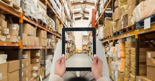 Πρόσωπο που φωτογραφίζει την αποθήκη εμπορευμάτων μέσω του PC ταμπλετών στοκ φωτογραφίες