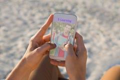 Πρόσωπο που χρησιμοποιεί ένα τηλέφωνο με την ε-εκμάθηση των πληροφοριών στην οθόνη στοκ εικόνες