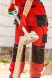 Πρόσωπο που χρησιμοποιεί το φτυάρι στο εργοτάξιο οικοδομής στοκ εικόνα με δικαίωμα ελεύθερης χρήσης