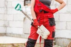 Πρόσωπο που χρησιμοποιεί το φτυάρι στο εργοτάξιο οικοδομής στοκ εικόνα