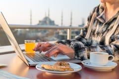 Πρόσωπο προγευμάτων εργασίας που εργάζεται στο lap-top στο πεζούλι καφέδων στοκ φωτογραφία