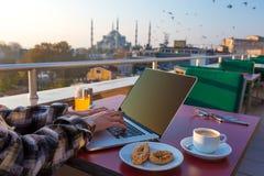 Πρόσωπο προγευμάτων εργασίας που εργάζεται στο lap-top στο πεζούλι καφέδων στοκ φωτογραφίες με δικαίωμα ελεύθερης χρήσης