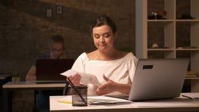 Πρόσωπο σκέψης στο καυκάσιο επιχειρησιακό κορίτσι που εναρμονίζει τα έγγραφά της, καθμένος στον εργασιακό χώρο με το lap-top απόθεμα βίντεο