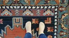 Πρόσωπο στα τζιν και τις κάλτσες μαλλιού που στέκονται στον παραδοσιακό σλαβικό τάπητα στοκ φωτογραφία
