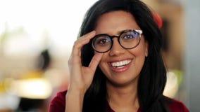 Πρόσωπο της ευτυχούς χαμογελώντας νέας γυναίκας στα γυαλιά απόθεμα βίντεο