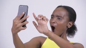 Πρόσωπο της νέας όμορφης αφρικανικής γυναίκας χρησιμοποιώντας το τηλέφωνο και συγκλονισμένος απόθεμα βίντεο