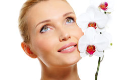 Πρόσωπο της όμορφης γυναίκας χαμόγελου με άσπρο orchid Στοκ φωτογραφία με δικαίωμα ελεύθερης χρήσης