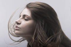 Πρόσωπο της όμορφης νέας γυναίκας με το πέταγμα τριχώματος στοκ φωτογραφία