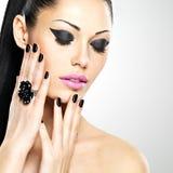 Πρόσωπο της όμορφης γυναίκας με τα μαύρα καρφιά και τα ρόδινα χείλια Στοκ Φωτογραφίες