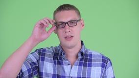 Πρόσωπο του ταραγμένου νέου ατόμου hipster που αφαιρεί eyeglasses απόθεμα βίντεο