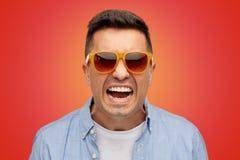 Πρόσωπο του υ ατόμου στο πουκάμισο και των γυαλιών ηλίου πέρα από το κόκκινο Στοκ φωτογραφία με δικαίωμα ελεύθερης χρήσης