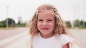 Πρόσωπο του χαμογελώντας μικρού κοριτσιού με τα ευτυχή μάτια στη θερινή πόλη απόθεμα βίντεο