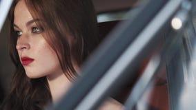 Πρόσωπο του όμορφου κοριτσιού με το σταθερό βλέμμα, που κάθεται πίσω από μια ρόδα ενός αυτοκινήτου απόθεμα βίντεο