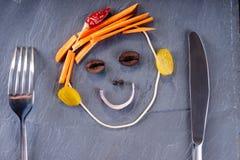 Πρόσωπο Smiley που γίνεται από τα λαχανικά, το μαχαίρι και το δίκρανο Στοκ φωτογραφίες με δικαίωμα ελεύθερης χρήσης