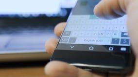Πρόσωπο Texting σε μια συσκευή smartphone lap-top στο υπόβαθρο απόθεμα βίντεο