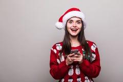 Πρότυπα καπέλο santa ένδυσης κοριτσιών και κείμενο πουλόβερ Χριστουγέννων sms στο τηλέφωνο Στοκ Εικόνα
