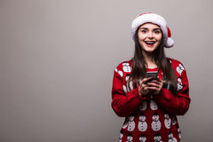 Πρότυπα καπέλο santa ένδυσης κοριτσιών και κείμενο πουλόβερ Χριστουγέννων sms στο τηλέφωνο Στοκ φωτογραφίες με δικαίωμα ελεύθερης χρήσης