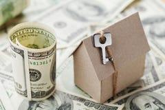 Πρότυπα σπίτι χαρτονιού, κλειδί και χρήματα δολαρίων Οικοδόμηση, ασφάλεια, εγκαίνια σπιτιού, δάνειο, ακίνητη περιουσία, κόστος τη Στοκ Εικόνα