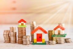 Πρότυπα σπιτιών με τα συσσωρευμένα νομίσματα στο ξύλινο προτέρημα γ επιτραπέζιων επιχειρήσεων Στοκ φωτογραφία με δικαίωμα ελεύθερης χρήσης