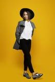 Πρότυπες δαπάνες κοριτσιών σε ένα κίτρινο υπόβαθρο με ένα καπέλο και ένα παλτό Στοκ εικόνες με δικαίωμα ελεύθερης χρήσης