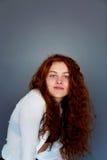 Πρότυπες δοκιμές Όμορφο redhead κορίτσι με τη σγουρή τρίχα Φυσικό χρώμα Πορτρέτο σε ένα γκρίζο υπόβαθρο στούντιο Στοκ Φωτογραφία