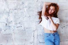 Πρότυπες δοκιμές Όμορφο redhead κορίτσι με τη σγουρή τρίχα Φυσικό χρώμα Στάσεις με το μακρυμάλλες φύσηγμα ενάντια στο ελαφρύ τούβ Στοκ Εικόνα