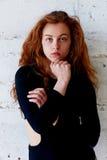Πρότυπες δοκιμές Όμορφο redhead κορίτσι με τη σγουρή τρίχα Φυσικό χρώμα Πορτρέτο Krupneishego σε ένα υπόβαθρο του ελαφριού τούβλο Στοκ Φωτογραφία