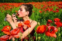 Πρότυπη γυναίκα μόδας ομορφιάς με τα κόκκινα λουλούδια παπαρουνών στοκ φωτογραφία με δικαίωμα ελεύθερης χρήσης