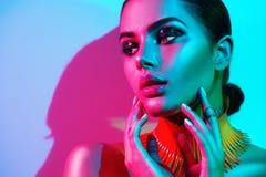 Πρότυπη γυναίκα μόδας στα ζωηρόχρωμα φωτεινά φω'τα με το καθιερώνοντα τη μόδα makeup και το μανικιούρ στοκ εικόνα