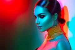 Πρότυπη γυναίκα μόδας στη ζωηρόχρωμη φωτεινή τοποθέτηση φω'των