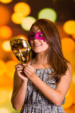 Πρότυπη γυναίκα ομορφιάς που φορά τη ρόδινη μάσκα καρναβαλιού με μια χρυσή μάσκα στα χέρια της Στοκ εικόνα με δικαίωμα ελεύθερης χρήσης