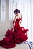 Πρότυπη γυναίκα Brunette ομορφιάς στο κόκκινο φόρεμα βραδιού στοκ φωτογραφίες με δικαίωμα ελεύθερης χρήσης
