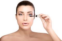 Πρότυπη νέα γυναίκα ομορφιάς που εφαρμόζει mascara Στοκ Εικόνες