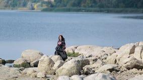 Πρότυπη τοποθέτηση Brunette σε μια όχθη ποταμού φιλμ μικρού μήκους