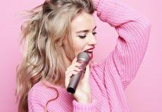 Πρότυπος τραγουδιστής κοριτσιών ομορφιάς με ένα μικρόφωνο πέρα από το ρόδινο υπόβαθρο Στοκ φωτογραφίες με δικαίωμα ελεύθερης χρήσης