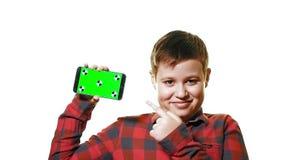 Πρότυπο έννοιας Εύθυμο αγόρι που κρατά ένα smartphone στο χέρι του με μια πράσινη οθόνη και τα γέλια απόθεμα βίντεο