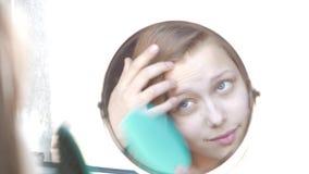 Πρότυπο έφηβη ομορφιάς που κοιτάζει στον καθρέφτη και που κτενίζει την τρίχα 4K φιλμ μικρού μήκους