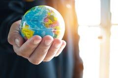 Πρότυπο γήινων σφαιρών εκμετάλλευσης επιχειρηματιών στα χέρια Έννοια για το glob στοκ φωτογραφία