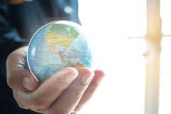Πρότυπο γήινων σφαιρών εκμετάλλευσης επιχειρηματιών στα χέρια Έννοια για το glob στοκ εικόνες